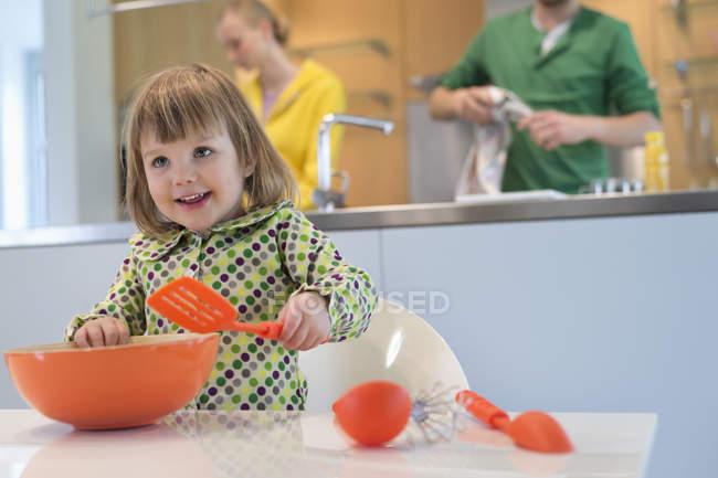 Linda niña con cuchara ranurada y tazón de mezcla en la cocina - foto de stock