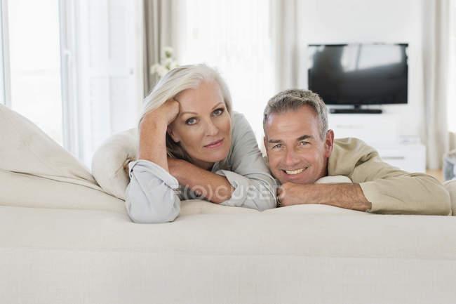 Retrato de sonriente pareja senior, reposo en cama en casa - foto de stock