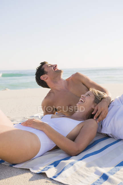 Relaxed laughing couple resting on sandy beach — Stockfoto