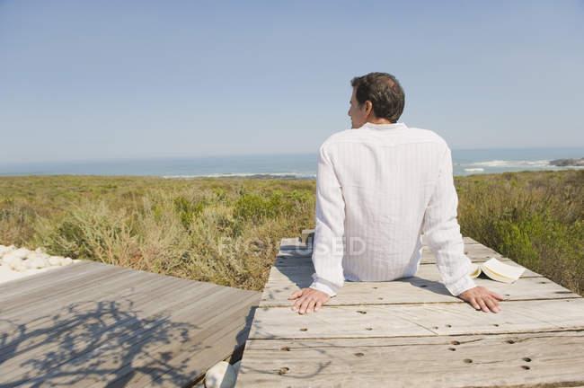 Vista posteriore dell'uomo seduto sul lungomare sulla costa e guardando la vista — Foto stock