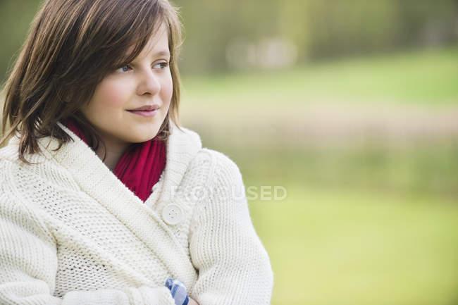 Adolescent réfléchi fille regardant loin dans le parc sur fond flou — Photo de stock