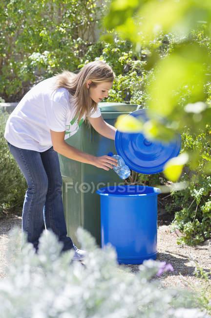 Femme jetant une bouteille d'eau dans la poubelle — Photo de stock