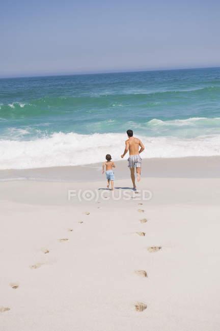 Следы на песчаном пляже с человеком работает с сыном на заднем плане — стоковое фото