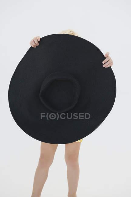 Little girl hiding behind big black hat on white background — Stock Photo