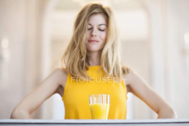 Женщина в жёлтом наряде смотрит на стакан апельсинового сока — стоковое фото