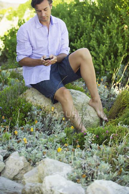 Mensagens de texto de homem adulto intermediário com telefone celular enquanto sentado na rocha no jardim — Fotografia de Stock