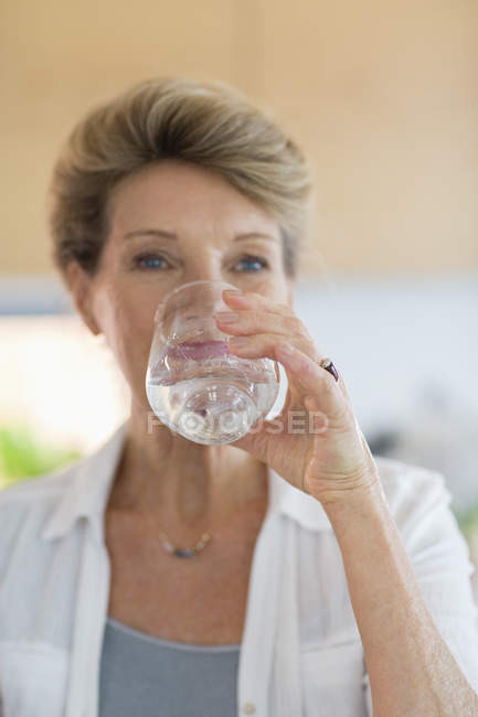 Close-up of senior woman drinking water from glass — Stock Photo