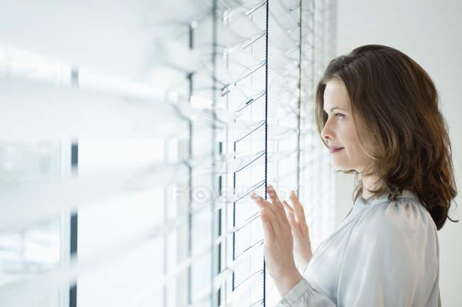 Donna premurosa che osserva dalla finestra in camera — Foto stock
