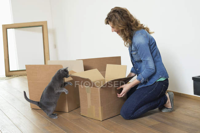 Woman looking at cat in apartment and smiling — Stock Photo