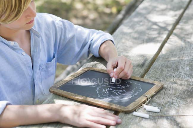 Мальчик-подросток рисует дерево на свежем воздухе — стоковое фото