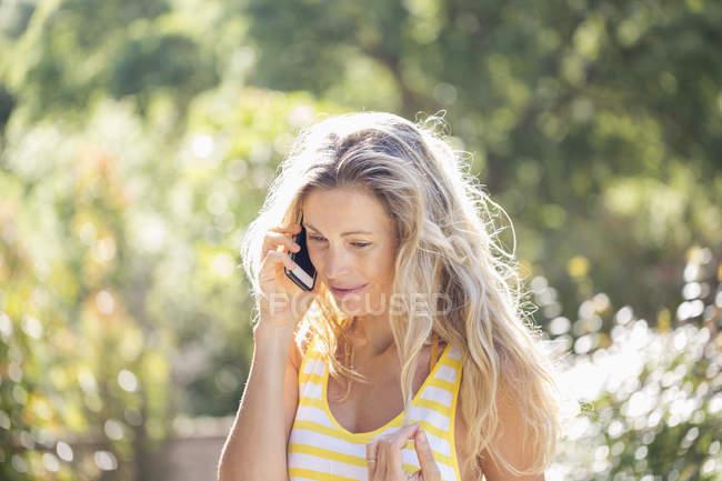 Lächelnde Frau am Telefon im sonnigen Garten — Stockfoto