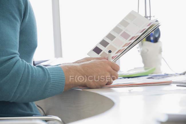 Mani del progettista che tiene campione di colore in ufficio — Foto stock