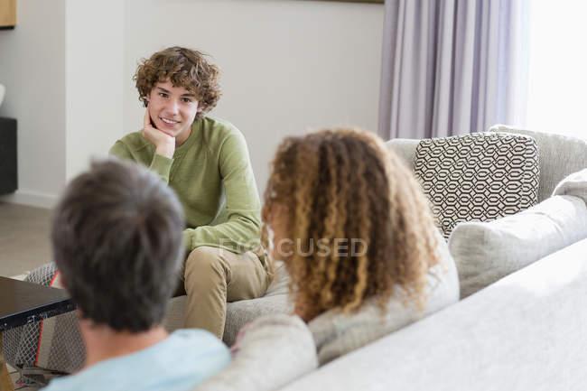 Улыбающийся мальчик говорить родителям, сидя на диване в гостиной в доме — стоковое фото