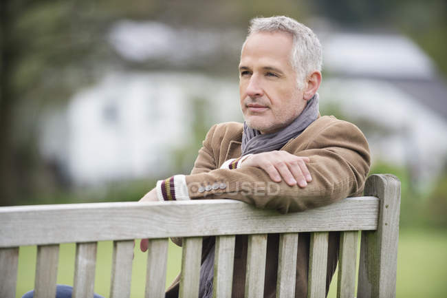 Thoughtful mature man sitting on bench in park — Stock Photo