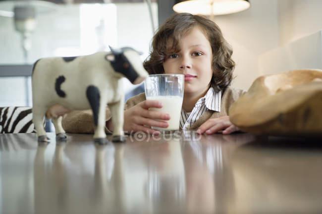Porträt eines lächelnden Jungen, der mit einem Glas Milch am Tisch sitzt — Stockfoto