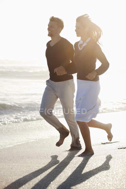 Sonriente pareja corriendo en la playa bajo la luz solar las manos - foto de stock