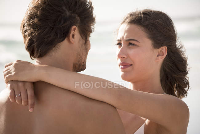 Close-up of young woman embracing boyfriend on beach — Stock Photo
