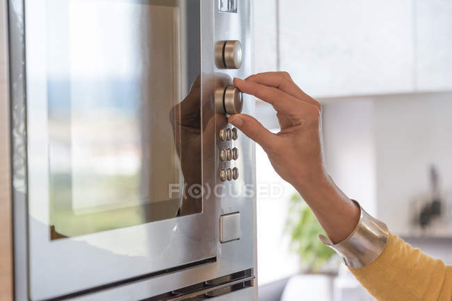Close-up of female hand switching button of microwave — Stock Photo