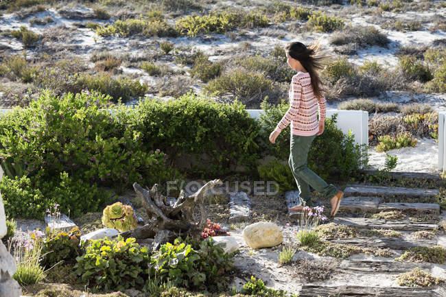 Woman walking on sunny coast with vegetation — Stock Photo