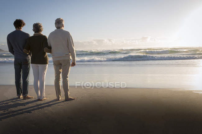 Family standing on beach beach together and looking at sea view — Stock Photo