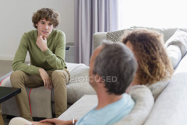 Smiling boy talking to parents while sitting on sofa in living room at home — Stock Photo