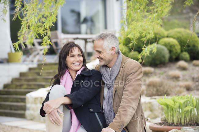 Романтическая пара, сидящая в саду и улыбающаяся — стоковое фото