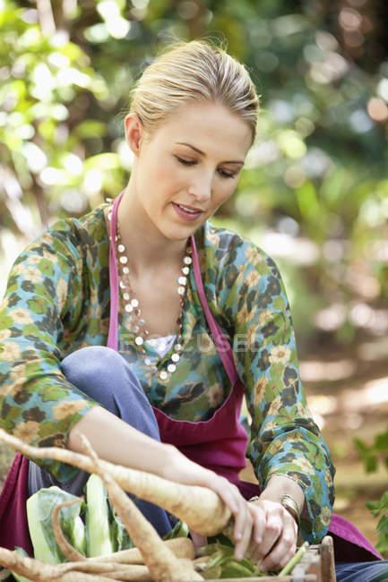 Femme tenant frais radis cueillies dans le jardin — Photo de stock