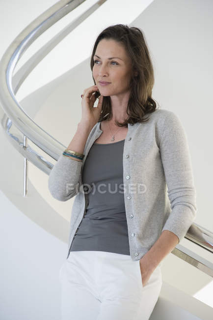 Thoughtful mature woman standing on staircase and looking away — Stock Photo