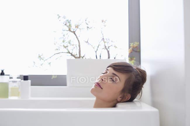Tranquila joven con los ojos cerrados relajándose en la bañera - foto de stock