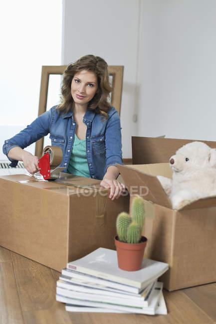 Portrait de femme en attachant du ruban adhésif boîte de carton dans l'appartement — Photo de stock