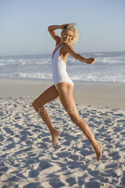 Happy young woman in swimsuit jumping on sandy beach — Stock Photo