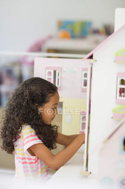 Little girl playing with dollhouse in room — Stock Photo