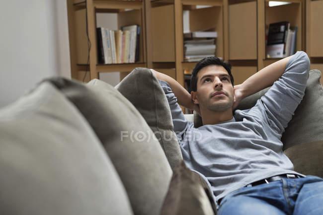Мрійливий людини, лежачи на канапі в домашніх умовах — стокове фото