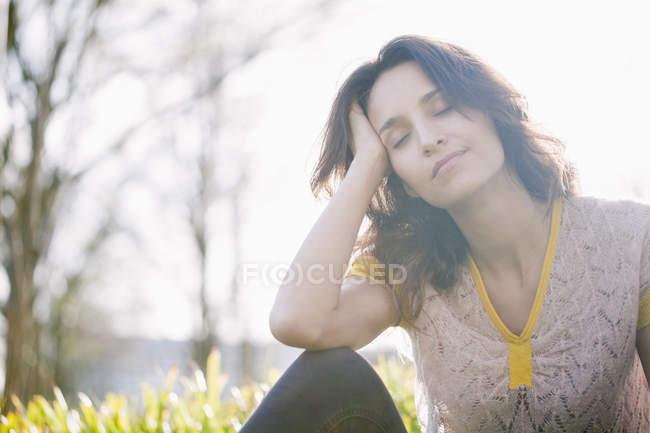 Мрійливий жінка з очі закриті відпочинку на природі — стокове фото