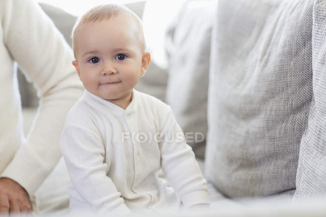 Happy baby girl sitting on couch at home — Stock Photo