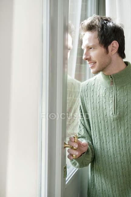 Человек в пуловере смотрит через стекло двери — стоковое фото