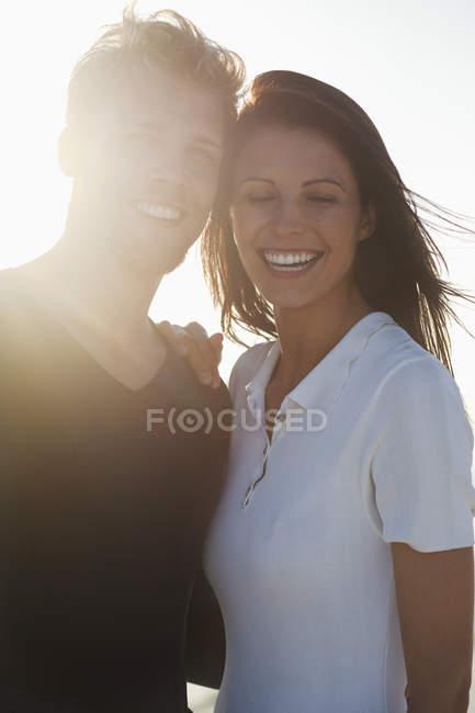 Primer plano de la sonrisa permanente de pareja juntos en la luz del sol - foto de stock