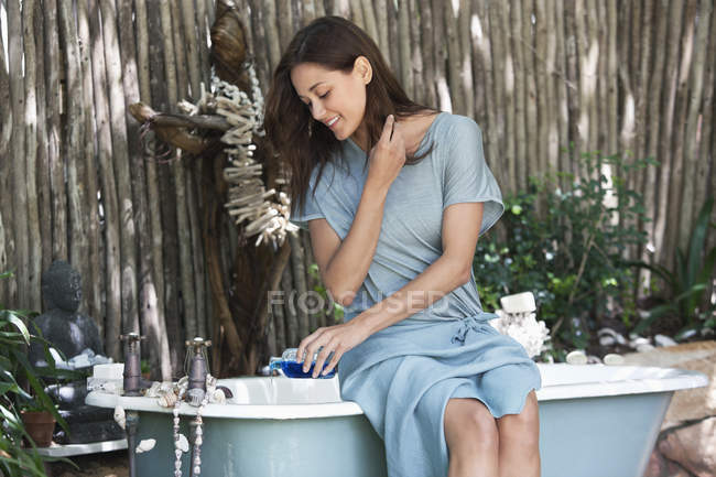 Young woman pouring aromatherapy oil in bathtub — Stock Photo