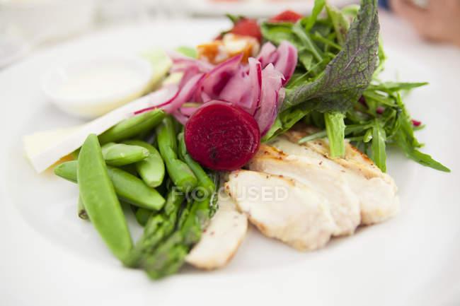 Primer plano de ensalada verde con espárragos, frijoles, rodajas de cebolla y otras verduras - foto de stock
