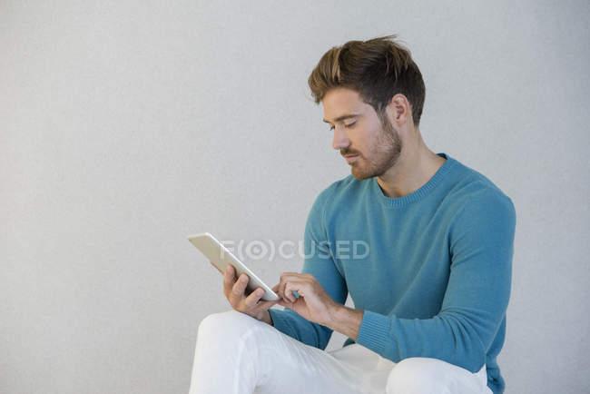 Giovane uomo che utilizza tablet digitale contro muro grigio — Foto stock