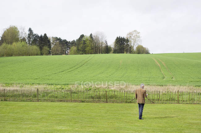 Man using mobile phone in green field — Stock Photo