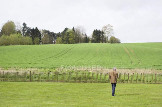 Uomo che utilizza il telefono cellulare in campo verde — Foto stock
