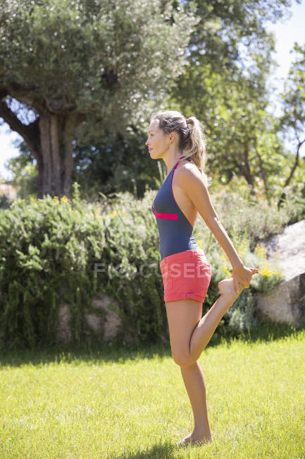 Woman standing on one leg while exercising in garden — Stock Photo