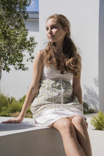Задумчивая девочка-подросток сидит на краю стены и смотрит в сторону — стоковое фото