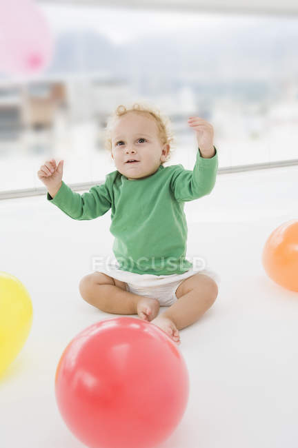 Cute baby boy playing with balloons on floor — Stock Photo