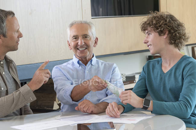 Smiling grandfather giving teenage grandson pocket money at table at home — Stock Photo
