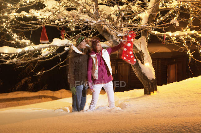 Young couple touching Christmas stocking hanging on tree at night — Stock Photo