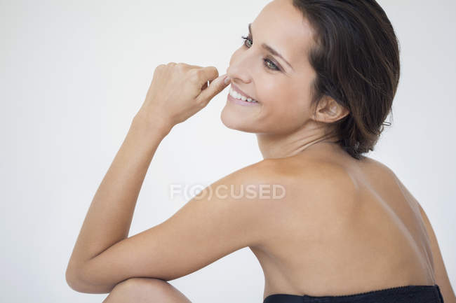 Elegante donna sorridente su sfondo bianco — Foto stock