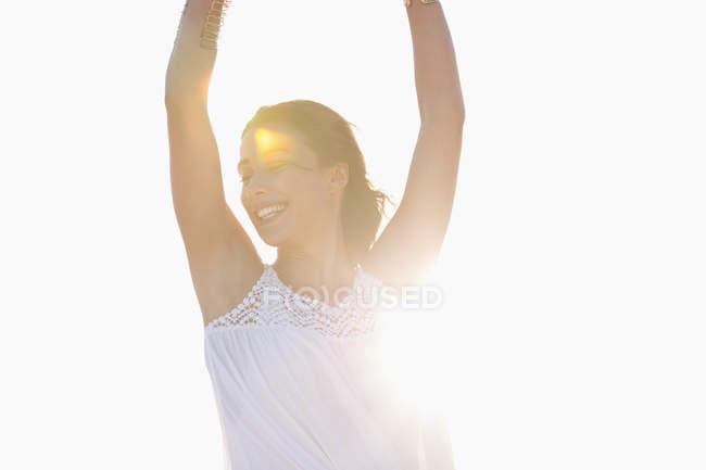 Jeune femme heureuse avec les bras levés posant sur la plage au soleil — Photo de stock