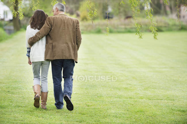 Opinião traseira o homem que anda com a filha no gramado verde — Fotografia de Stock